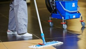31179301 - cleaner with mop and uniform cleaning hall floor of public business building